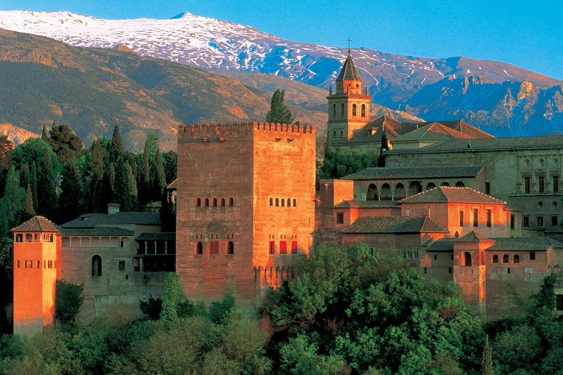 Den vidunderlige paladsby Alhambra med de sneklædte Sierra Nevada-bjerge i baggrunden