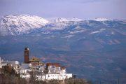 Byen Laroles med sneklædte bjerge i baggrunden