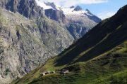 Udsigt over bjerghytter med sneklædt bjergtop i baggrunden