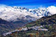 Udsigt over den lille by Capileira med de sneklædte Sierra Nevada-bjerge i baggrunden